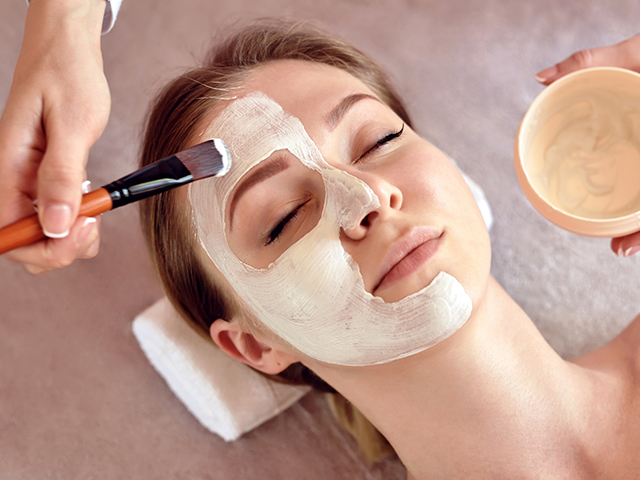 Face peeling mask, spa beauty treatment, skincare. Woman getting facial care by beautician at spa salon, close-up