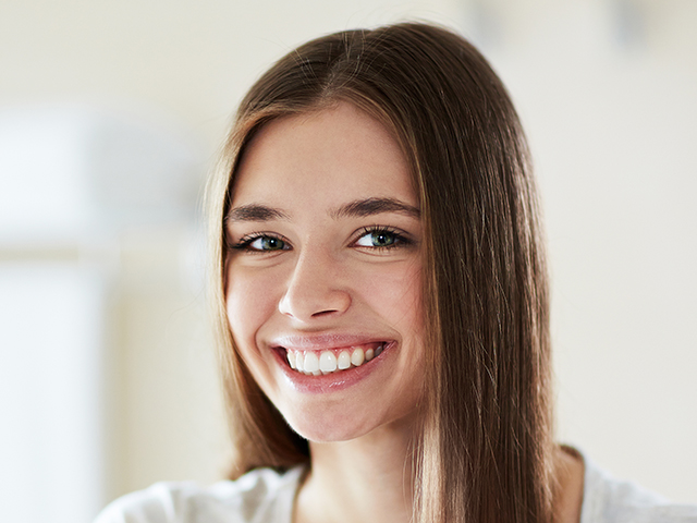 Young beautiful woman with perfect teeth smiling at mirror